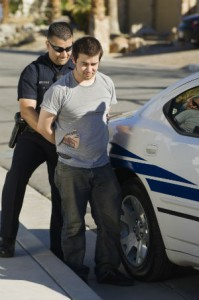Police Man Arresting A Young Man In Front Of Car